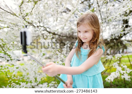 Adorable little girl taking a photo of herself with a selfie stick on beautiful summer day - stock photo