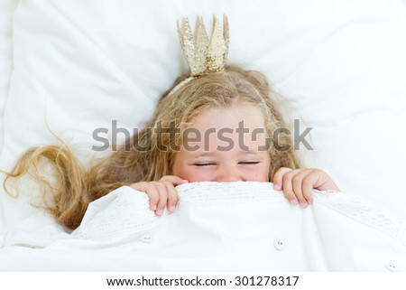 Adorable little girl wake up in her bed - stock photo