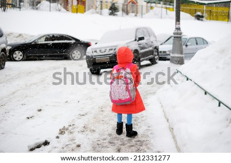 Adorable little girl walking from school on winter day in the city - stock photo