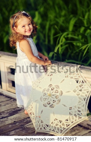 adorable little girl walking in the park with sun umbrella - stock photo