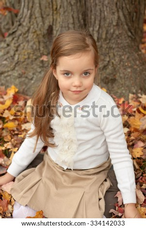 adorable little girl wearing a white sweater siting on a ground and smiling on a warm autumn day - stock photo