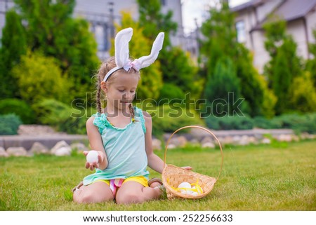 Adorable little girl wearing bunny ears holding basket with Easter eggs - stock photo