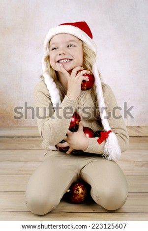 Adorable little girl wearing christmas hat and holding christmas balls - stock photo
