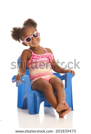 Adorable little girl wearing sun glasses and sitting in a beach chair.  Isolated on white with room for your text. - stock photo