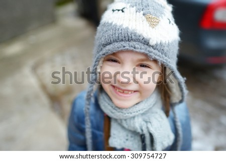 Adorable little girl wearing winter hat making funny faces on beautiful winter day outdoors - stock photo
