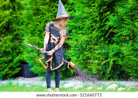 Adorable little girl wearing witch costume with broom on Halloween outdoors - stock photo