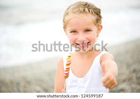 Adorable little girl with a candy on show the thumb - stock photo