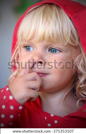Adorable little girl with a funny face wearing red hoodie is digging her nose - stock photo
