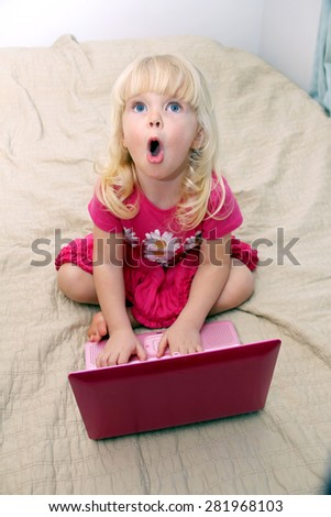 Adorable little girl with a funny surprised face typing on laptop - stock photo