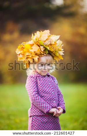 Adorable little girl with a wreath of maple leaves on head on beautiful autumn day - stock photo