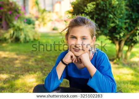 Adorable little girl with beautiful blue eyes sitting in backyard and looking at camera. Shallow depth of field. - stock photo