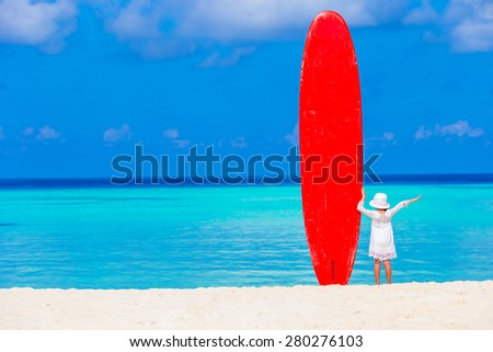 Adorable little girl with big surfboard during tropical vacation - stock photo