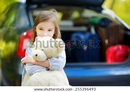 Adorable little girl with big teddy bear leaving for a car vacation with her parents - stock photo