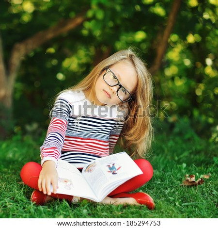 Adorable little girl with book in a summer park wearing glasses  - stock photo