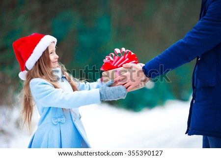 Adorable little girl with christmas box gift in winter outdoors - stock photo