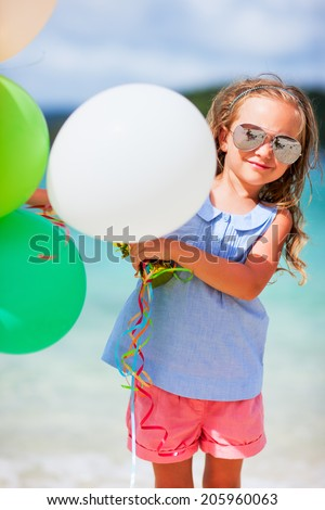 Adorable little girl with colorful balloons at beach during summer vacation - stock photo