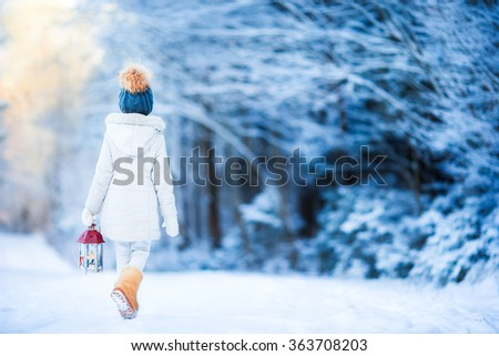Adorable little girl with flashlight in winter on Christmas outdoors - stock photo