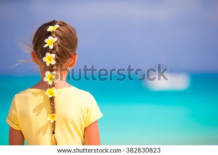 Adorable little girl with frangipani flowers in hair on beach  - stock photo