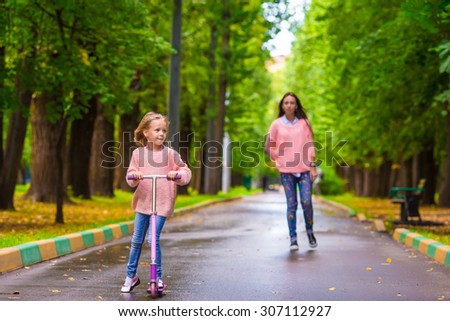 Adorable little girl with happy mom have fun on the scooter outdoor - stock photo