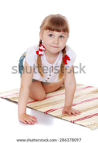 Adorable little girl with long braids on his head plays on the rug . Montessori kindergarten-Isolated on white background - stock photo