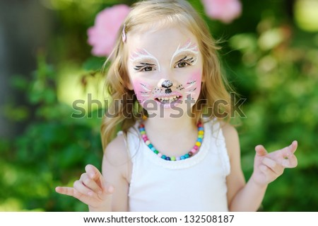 Adorable little girl with painted face - stock photo