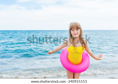 Adorable little girl with pink inflatable ring by the sea on summer vacation - stock photo