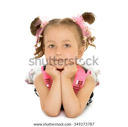 Adorable little girl with pretty pigtails on his head, lying on the floor with his head in his hands . Closeup - Isolated on white background.The concept of a Happy childhood and child development - stock photo