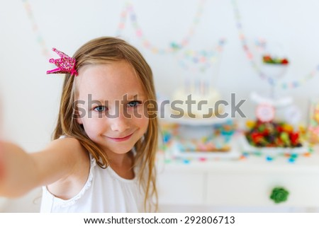 Adorable little girl with princess crown at kids birthday party taking selfie - stock photo