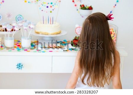 Adorable little girl with princess crown on a birthday party near dessert table - stock photo