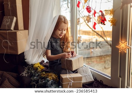 Adorable little girl with red hair in a room near the window with gifts. Christmas holidays. In anticipation of the holiday - stock photo
