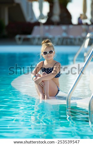 Adorable little girl with sunglasses by the swimming pool  - stock photo