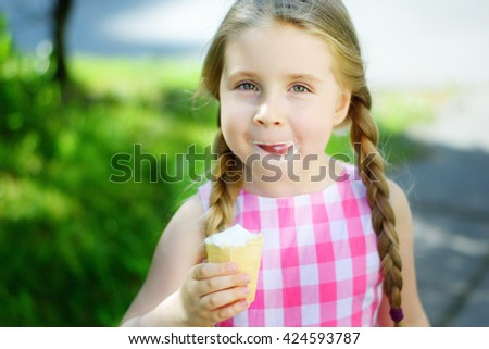 Adorable little girl with tasty ice cream on summer - stock photo