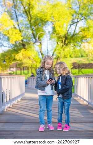 Adorable little girls at warm autumn day outdoors - stock photo