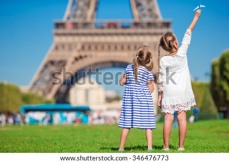 Adorable little girls in Paris background the Eiffel tower during summer vacation - stock photo