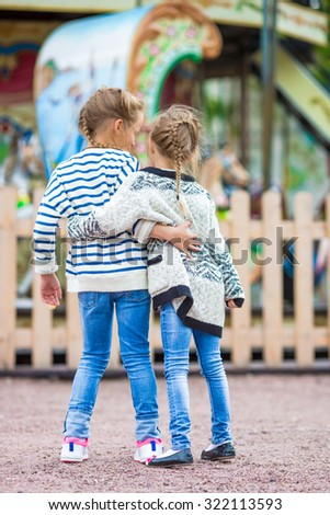 Adorable little girls near the carousel outdoors - stock photo