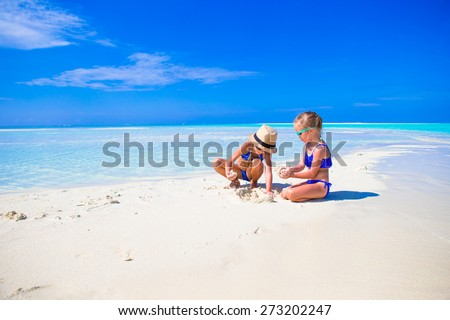 Adorable little girls on beach during summer vacation - stock photo