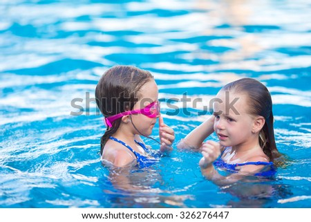 Adorable little girls playing in outdoor swimming pool on vacation - stock photo