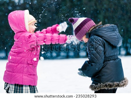 Adorable Little Girls Playing in the Snow Together - stock photo