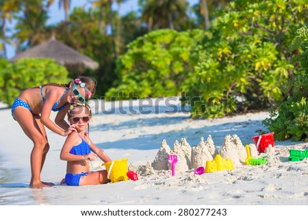 Adorable little girls playing with beach toys during tropical vacation - stock photo