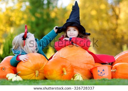 Adorable little girls wearing halloween costume having fun on a pumpkin patch - stock photo
