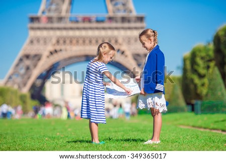 Adorable little girls with map of Paris background the Eiffel tower - stock photo