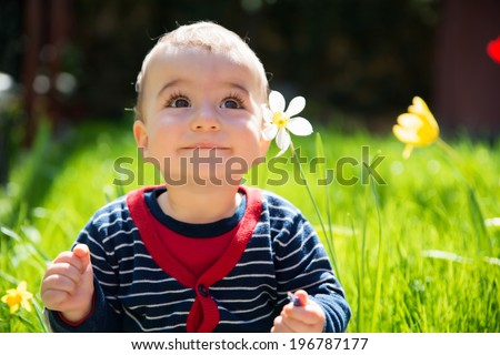 Adorable little happy smiling baby boy playing in a blooming garden between the flowers - stock photo