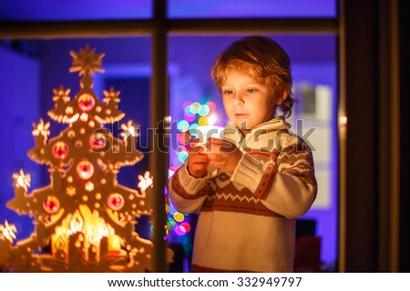 Adorable little kid boy, blond child standing by window at Christmas time and holding candle. With colorful lights from Christmas tree on background. Holiday, lifestyle, xmas concept - stock photo
