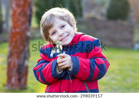 Adorable little kid boy in red jacket holding snowdrop flowers outdoors on sunset. Child making gift for mum and dad. - stock photo