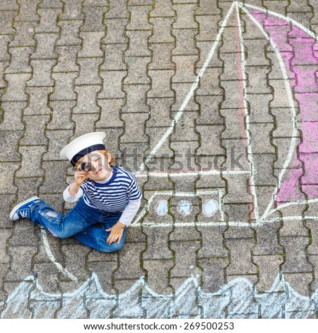 Adorable little kid boy playing with colorful chalks and painting ship or boat picture. Creative leisure for children outdoors in summer - stock photo