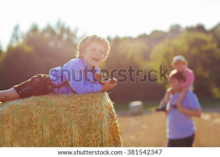 Adorable little kid boy sitting on hay stack or bale and eating traditional pretzel. Child in bavarian clothes. Father and brother on background - stock photo