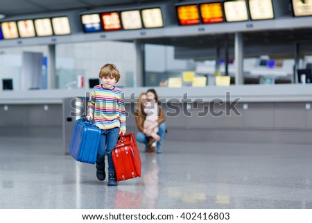 Adorable little kid boy with red and blue suitcases on international airport. Mother and daughter on background, happy family wating for flight and going on vacations. - stock photo