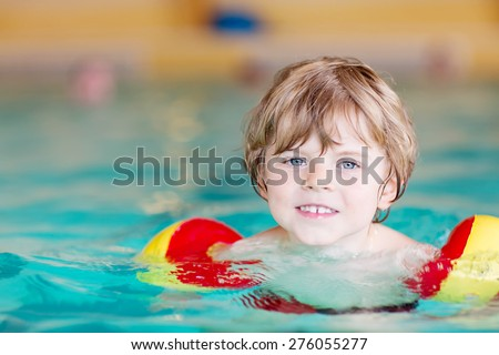 Adorable little kid boy with swimmies learning to swim in an indoor pool. Active and fit leisure for children. - stock photo