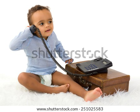 Adorable little 18 month old toddler boy of African decent playing with a telephone - stock photo