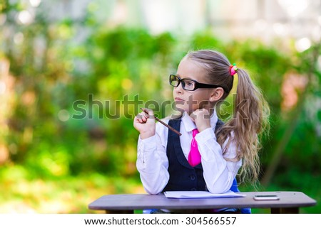 Adorable little school girl at desk with notes and pencils outdoor. Back to school. - stock photo